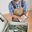 Electrician Looking At Fuse Box — Stock Photo #74747831