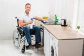 Man On Wheelchair Cleaning Stove — Stock Photo
