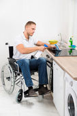 Handicapped Man Cleaning Induction Stove — Stock Photo