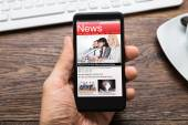 Hand With Mobile Phone Showing News — Stock Photo