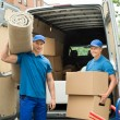 Workers Carrying Carpet And Cardboard Boxes — Stock Photo #80378100