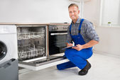 Разнорабочий с буфером обмена, глядя на Посудомоечная машина — Стоковое фото