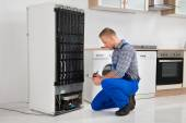 Plumber Writing On Clipboard In Front Of Refrigerator — Stock Photo