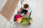 Man Putting Clothes In Washing Machine — Stock Photo