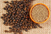 Black pepper on hessian fabric — Stock Photo