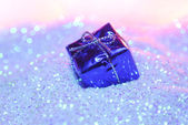 Gift box on glitter — Stock Photo