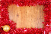 Christmas red tinsel frame border on wood surface — Stock Photo