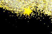 Golden glitter and star on black — Stockfoto