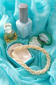 Perfume and bracelet on blue scarf — Photo