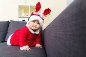 Baby girl with christmas dressing and creeping on sofa — Stock Photo