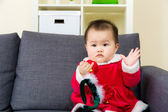 Baby girl seating on sofa with christmas dressing — Stock Photo