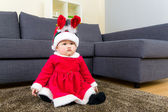 Baby girl with christmas dressing and seating on carpet — Stock Photo