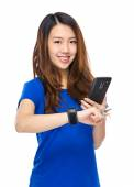 Woman use cellphone share date with wearable watch — Stock Photo