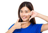 Asian woman with two finger frame in front of mouth — Stock Photo