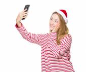 Woman with santa hat taking selfie — Stock Photo