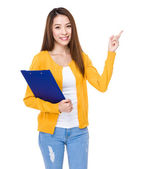 Woman with clipboard and finger point up — Stock Photo
