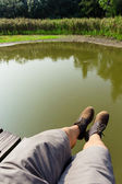 Male legs over the river — Stock Photo
