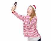 Woman with christmas hat taking selfie — Stok fotoğraf