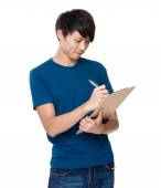 Asian man writes on clipboard — Stock Photo