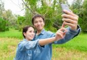 Asian couple taking selfie in park — Stock Photo