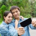 Asian couple taking selfie in park — Stock Photo #69623475