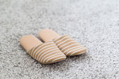 Slippers on gray carpet — Stock Photo