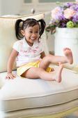 Adorable little girl sitting on sofa — Stock Photo