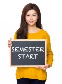 Asian woman in yellow sweater with blackboard — Stock Photo