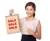 Asian woman point to shopping bags — Stock Photo