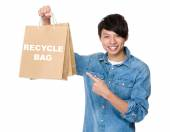 Asian man point to shopping bags — Stock Photo