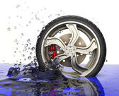 Car wheel with water splash — Stock Photo
