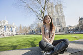Woman sitting against Westminster Abbey — Stock Photo