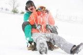 Oung couple sledding — Stock Photo