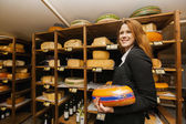 Salesperson holding cheese — Stock Photo