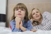 Boy and mother lying on bed — Stok fotoğraf