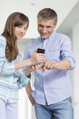 Father and daughter using smart phone — Stock Photo