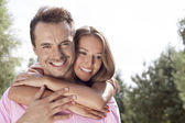 Happy young man being embrace by woman — Stock Photo
