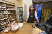 Saleswoman standing at cash counter — Stock Photo