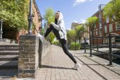 Woman stretching on sidewalk — Stock Photo