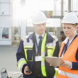 Workers discussing over clipboard — Stock Photo #57270609