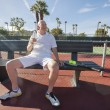 Tennis player sitting on bench — Stock Photo #57278089