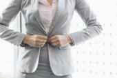 Businesswoman buttoning her blazer — Stock Photo