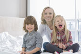 Mother with children smiling in bedroom — Stock Photo