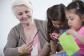 Woman helping granddaughters — Stock Photo