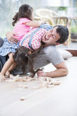 Playful daughters on top of father — Stock Photo