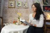 Woman reading book in cafe — Stok fotoğraf