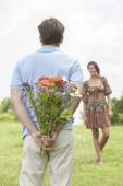 Man surprising woman with bouquet — Stock Photo