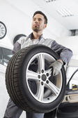 Maintenance engineer carrying tire — Stock Photo