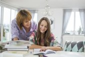 Mother assisting daughter in doing homework — 图库照片