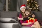 Girl hugging sister on sofa — Stock Photo